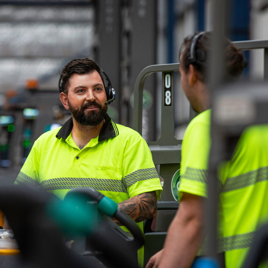 two logistics workers talking